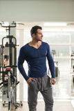Strong Man in Blue T-shirt Background Gym Stock Image