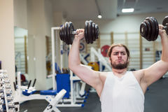 Strong man, bodybuilder exercising with dumbbells in a gym Royalty Free Stock Image