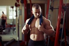 Strong man bodybuilder with towel on his neck in the gym relaxing Stock Image