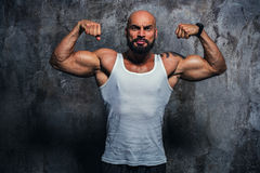 Strong man. Bodybuilder on wall background. Tattoo on body royalty free stock photo