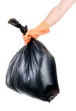 Strong man carry garbage in bag for eliminate. Strong man hand in orange gloves carry garbage in plastic bag for eliminate on the white background Royalty Free Stock Photos