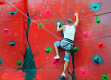 Strong man climbing on a climbing wall. Training in insurance stock images