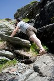 Strong man climbing mountain Stock Photography