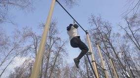 Strong man climbing on rope during outdoor workout on sport ground stock video footage