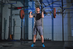 Strong man doing an exercise with a barbell in the gym on a background of a gray concrete wall. Man doing an exercise with a barbell in the gym on a background Royalty Free Stock Photo