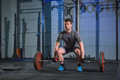 Strong man doing an exercise with a barbell in the gym on a background of a gray concrete wall. Man doing an exercise with a barbell in the gym on a background Royalty Free Stock Photography