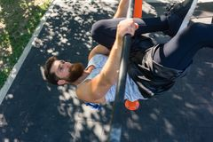 Strong man doing hanging leg raises for abdominal muscles. High-angle view of a strong and determined young man doing hanging oblique leg raises for abdominal royalty free stock photography