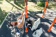 Strong man doing hanging leg raises for abdominal muscles during workout Royalty Free Stock Photos