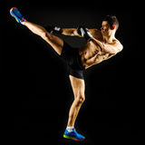 Strong man doing a high kick. Strong determined fit man doing a high kick stock images