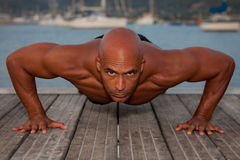Strong man doing press ups Stock Photography