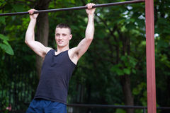 Strong man doing pull-ups on a bar outdoor Royalty Free Stock Image
