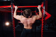 Strong man doing pull ups handsome athlete at gym. big confident muscular  training. Royalty Free Stock Photos