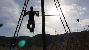 Strong Man doing Pull Ups under the Sun stock video