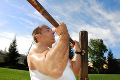 Strong Man Doing Pullups in the Park. On a Sunny Day Royalty Free Stock Photo