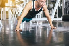 Strong man doing push up and exercises on floor at gym stock image