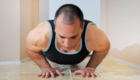 Strong Man Doing Pushups. Strong man in tank top doing push ups on the floor Stock Image