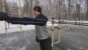 Strong man doing workout exercises with expander on outdoor training. Male winter training for development strength and endurance. Healthy lifestyle stock video
