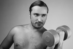 Strong man with dumbbells Stock Image