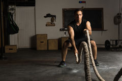 Strong man exercising with battle ropes. Portrait of an active and strong Latin man working out using battle ropes in a cross-training gym stock images