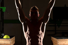 Strong man exercising in dramatic light Stock Image
