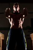 Strong man exercising in dramatic light Royalty Free Stock Images