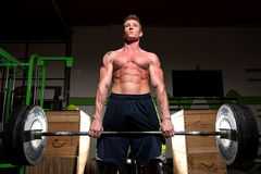 Strong man exercising in dramatic light Stock Photo