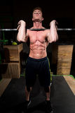 Strong man exercising in dramatic light Stock Photography