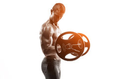 Strong man exercising fitness body building exercises with a barbell. Isolated on white background Whith solar flare Royalty Free Stock Image