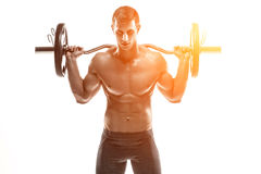 Strong man exercising fitness body building exercises with a barbell. Isolated on white background Whith solar flare Royalty Free Stock Photos