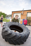 Strong man flips heavy tire outdoor as workout Stock Photography