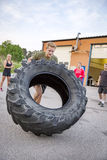 Strong man flips heavy tire outdoor as workout Stock Image