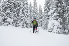 Strong man goes on snowshoes down the hill Royalty Free Stock Photos
