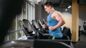 Strong man in the gym - bodybuilder running on the running track in the gym - slider. Shot stock footage