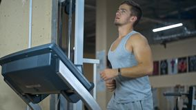 Strong man in the gym - bodybuilder running on the running track in the gym stock footage