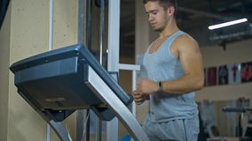 Strong man in the gym - bodybuilder running on the running track in the gym stock video footage