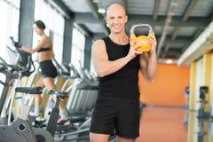 Strong man at the gym lifting kettlebell Royalty Free Stock Image