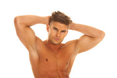 Strong man with hands behind head upper body. A man with a serious expression on his face flexing her body Stock Image
