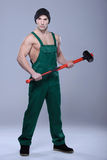 Strong Man. Handsome young topless construction worker with sledge hammer, studio shot, gray background Stock Photo