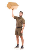 Strong man. Happy delivery man standing and holding carton box in raised hand. Full length studio shot isolated on white Royalty Free Stock Image