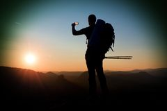 Strong man hiker taking photo with smart phone at mountain peak. Daybreak at horizon Stock Photography