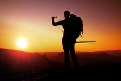 Strong man hiker taking photo with smart phone at mountain peak. Daybreak at horizon Stock Photo