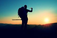 Strong man hiker taking photo with smart phone at mountain peak. Daybreak at horizon Stock Images