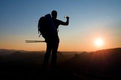 Strong man hiker taking photo with smart phone at mountain peak. Daybreak at horizon Royalty Free Stock Photo
