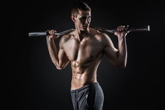 Strong man holding barbell on his shoulders, looking to side Stock Photography