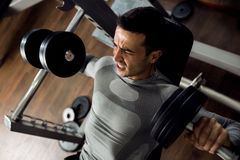 Strong man holding huge weight and working bench press. At gym Stock Photos