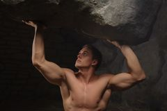 Strong man holding stone. Strong muscular man athlete atlant holding huge stone. Half length portrait. Symbol of power, burden Stock Photography