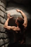 Strong man holding stone Stock Photo