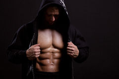 Strong man  in the hood showing his press on black background Royalty Free Stock Photo