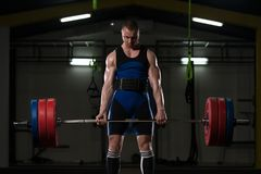 Powerlifter Heavy Weight Barbell Exercise Deadlift in Powerlifti. Strong Man Lifting Heavy Barbell From Floor During Powerlifting Workout in Gym stock image