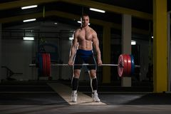 Powerlifter Heavy Weight Barbell Exercise Deadlift in Powerlifti. Strong Man Lifting Heavy Barbell From Floor During Powerlifting Workout in Gym stock photo